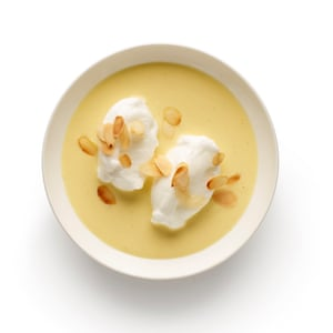 4 Divide the cold custard between bowls, and top each with two soft meringues and a scattering of nuts