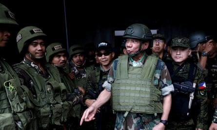The Philippine president, Rodrigo Duterte, in a bulletproof vest and helmet as he speaks to troops fighting in Marawi in August