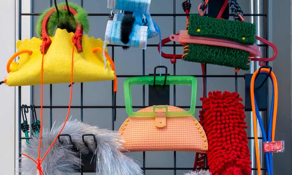 A collection of Clara Chu handbags made from household objects hanging from a black frame
