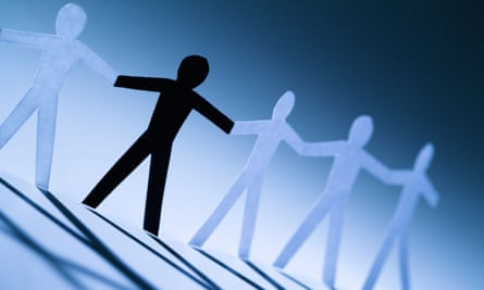A black cutout paper person holding hands with group of white people