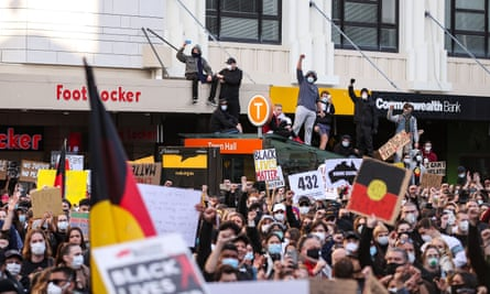 Protesters with Aboriginal flag in Sydney