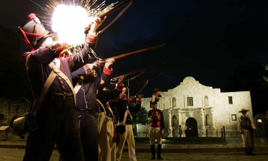 Dressed as Mexican soldiers, members of the San Antonio Living History Association fire a volley at the Alamo.