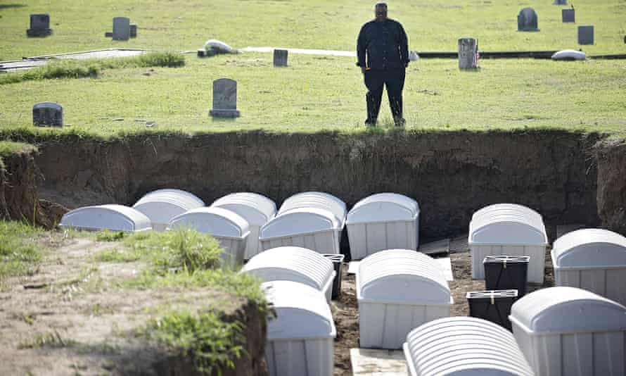 Graves public oversight committee chair J Kavin Ross views remains in a mass grave as they are reinterred at Oaklawn cemetery in Tulsa.