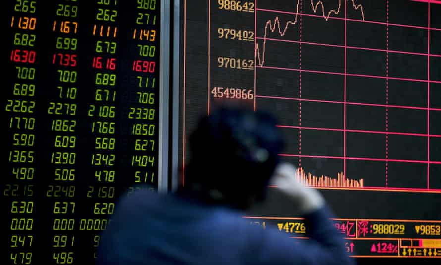 An investor looks at an electronic board displaying stock prices at a brokerage house in Beijing.