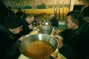 Men eat soup in the canteen during the lunch break.