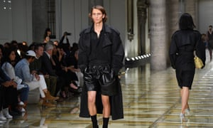 male model wearing a black trenchcoat and black shorts