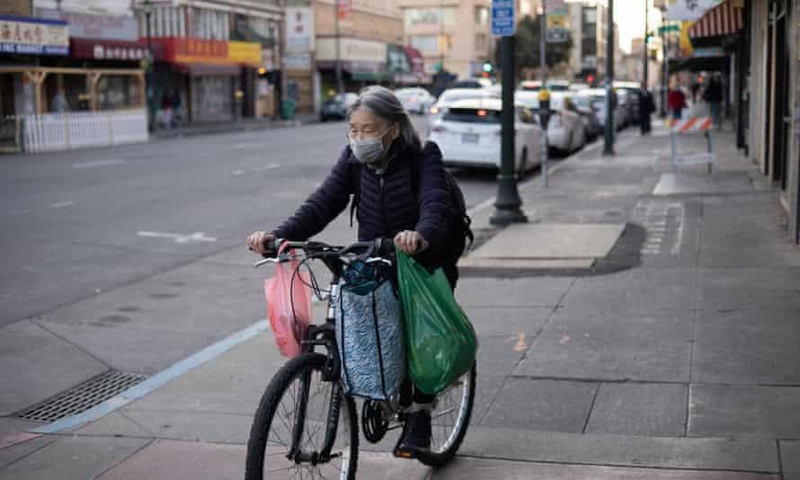 A woman rides a bike through Chinatown in Oakland, California.