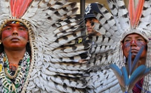 A police officer stands guard as indigenous leaders of the Huni Kuin Kaxinawá from Brazil join a protest organised by Extinction Rebellion against the Brazilian government's environmental polices, outside of the Brazilian Embassy in London.