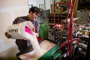 Head press operator Dave Mendoza hand mixing a custom color in the hopper