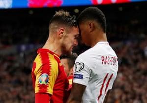 England's Marcus Rashford clashes with Montenegro's Marko Vesovic.