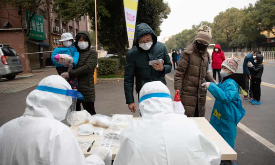 People who have been in close contact with Covid-19 sufferers are tested on a street in Wuhan, China.