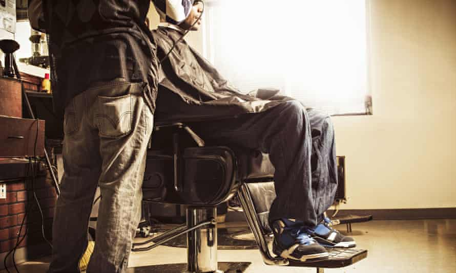 Barber in a traditional shop shaving man's head
