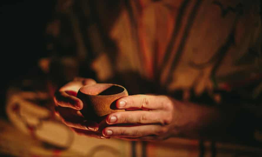 Person with a cup of ayahuasca.
