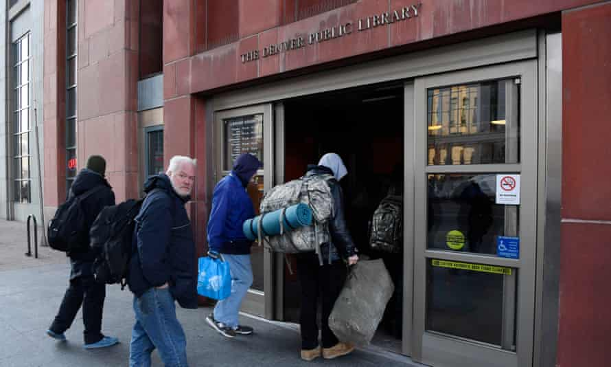 Mostly homeless people line up and wait to enter a Denver library to warm up and to use their resources.