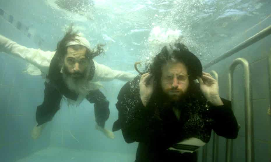 """Ori Gruder, left, and rabbi Yisrael Aharon Itzkovitz swim in their clothes in a ritual bath, which is created for publicity purpose for """"Sacred Sperm,"""" a film Gruder directed. Gruder created """"Sacred Sperm,"""" an hour-long documentary in which he tries to tackle the hard questions he can expect from his son."""