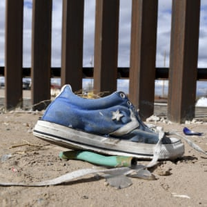 A shoe in front of the metal fence between Mexico and the United States in Puerto Anapra, Juarez