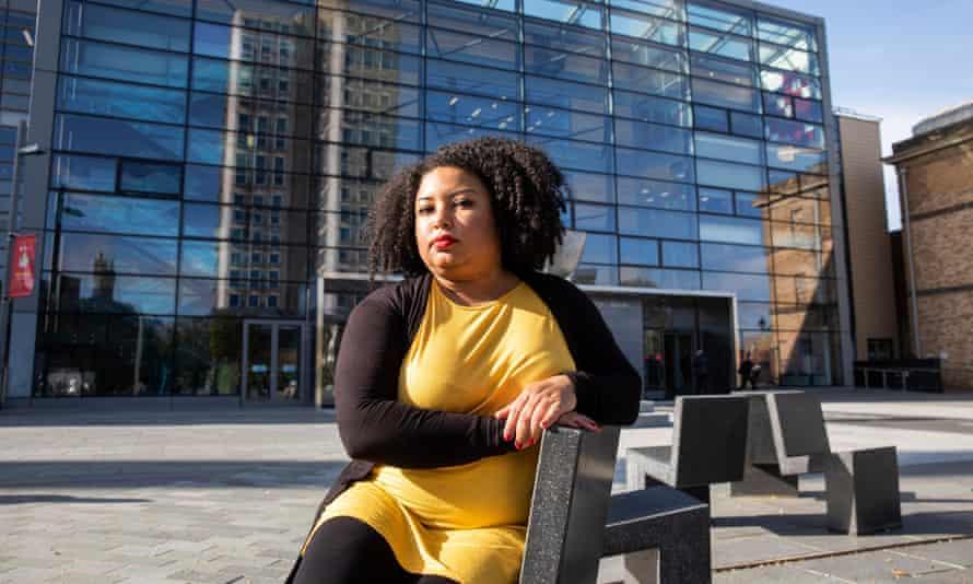 Furaha Asani sitting on bench outside modern   Leicester university building
