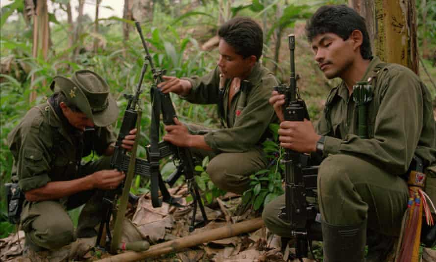 Rebels from the Revolutionary Armed Forces of Colombia (Farc) clean their rifles at a camp in the mountains near Miranda.