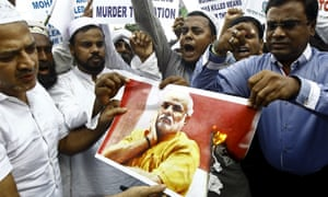 Demonstrators shout slogans as they burn a portrait of Narendra Modi during a protest in Kolkata