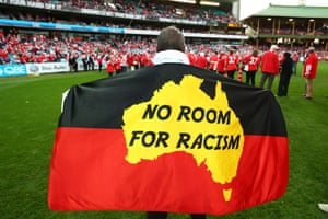 Fans display flags in support of Adam Goodes during the round 18 AFL match between the Sydney Swans and the Adelaide Crows at Sydney Cricket Ground in March.