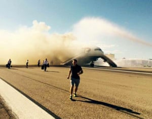 Passengers, including Jeremy Turnbull, front, flee from a British Airways plane alight at Las Vegas airport on 8 September 2015.