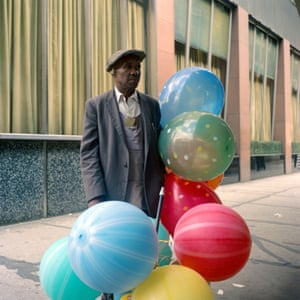 A man carrying several large multicoloured balloons