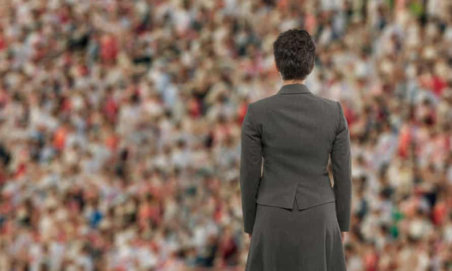 Woman standing facing away from us into a crowd