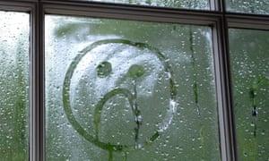 Sad face drawn in window condensation.