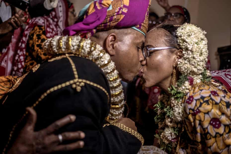 Surrounded by friends and family, the bride and groom share their first kiss at the bride's home in Domoni