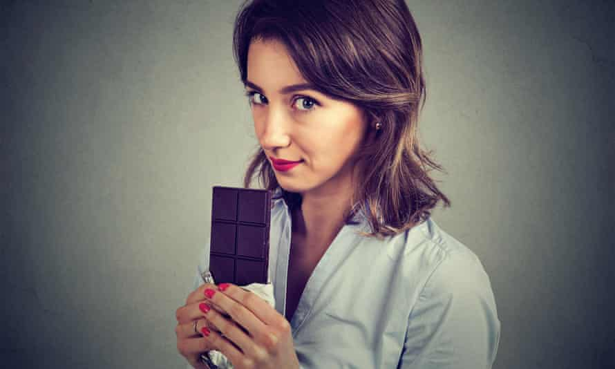 Closeup portrait of cute young woman eating a chocolate isolated on gray backgroundJWJ62A Closeup portrait of cute young woman eating a chocolate isolated on gray background