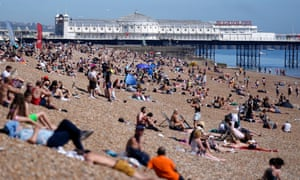 Beachgoers bask in the sun in Brighton.