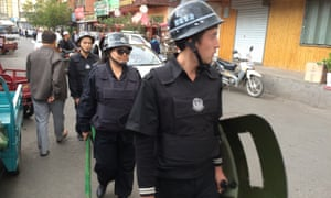 Police patrol a Uighur neighbourhood in Urumqi, the capital of Xinjiang.
