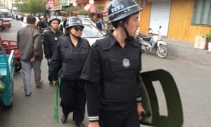 Police armed with wooden clubs patrol a Uighur neighbourhood in Urumqi, the capital of Xinjiang.