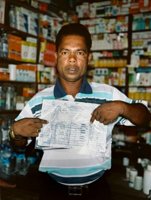 A man holds a copy of official documents confirming his family's Rohingya identity