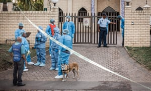Police investigators gather at the entrance to the Imam Hussain Mosque on the outskirts of Durban