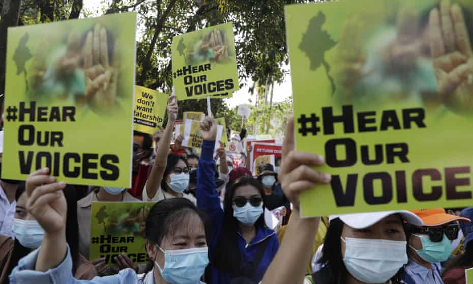 Protesters hold posters during a rally against the military coup in Yangon.