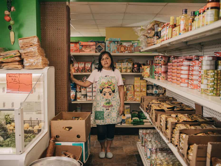 Maribel Lobato stands among the aisles of Veracruz Mexican market in Monroe, Wisconsin, surrounded by aisles of Mexican food products and a bin of fresh produce.