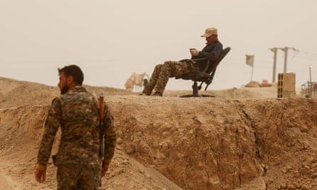 Fighter with the YPG – the Kurdish Peoples' Protection Units - reading book near Raqqa frontline