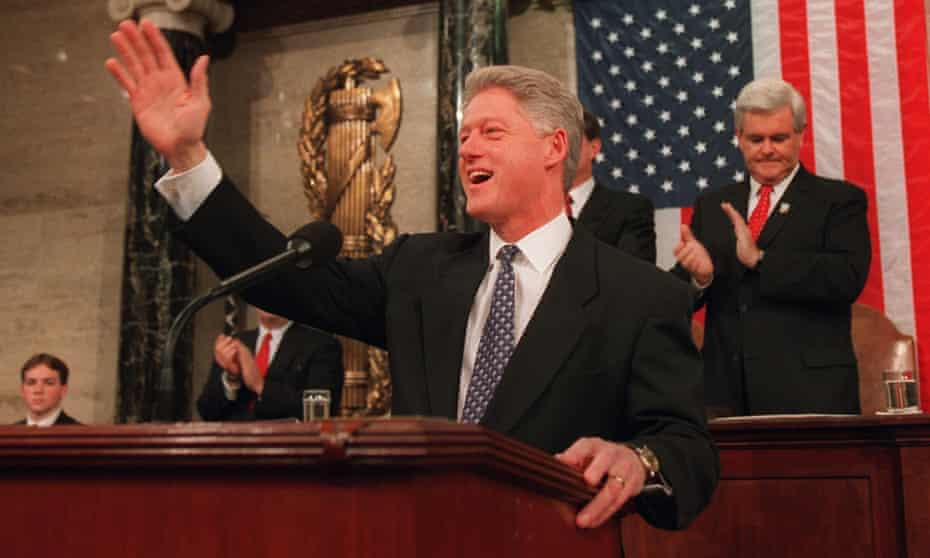 Bill Clinton waves from the podium before beginning his State of the Union address in February 1997, with Newt Gingrich behind him.