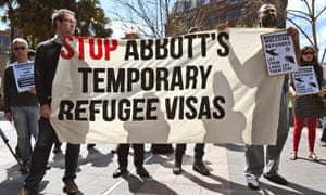 Protestors hold a sign that reads, 'Stop Abbott's temporary refugee visas'.