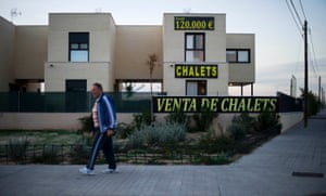 A man passes by a chalet for sale in Sesena, Spain.