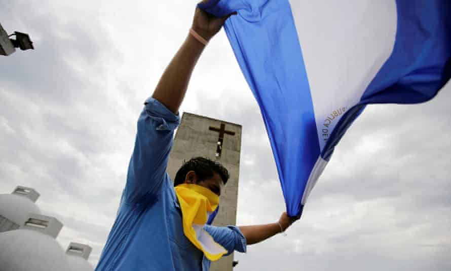 A man holds a national flag after a mass at the Metropolitan Cathedral in Managua, Nicaragua, to demand the release of demonstrators detained during protests against the government.