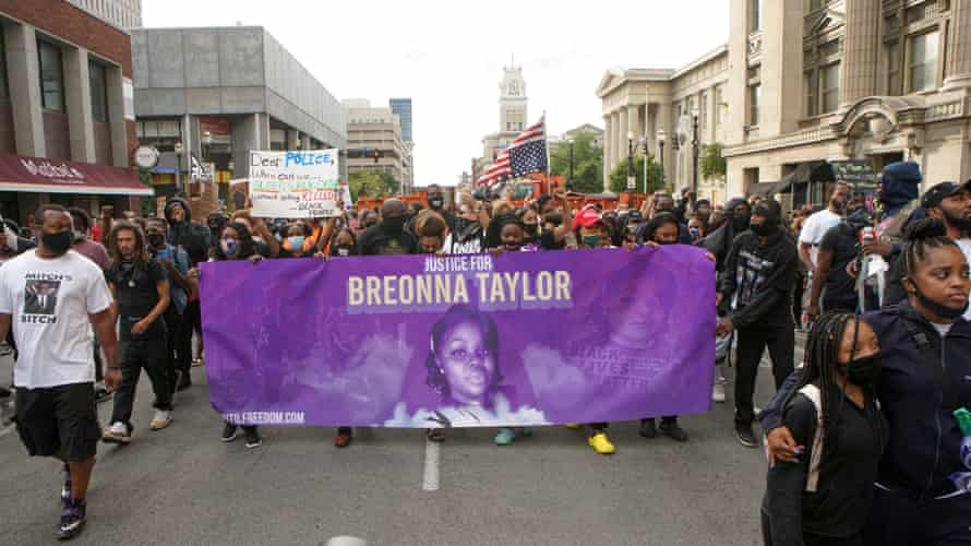 Protesters march through Louisville, Kentucky, after a grand jury decided not to bring homicide charges against police officers involved in the fatal shooting of Breonna Taylor
