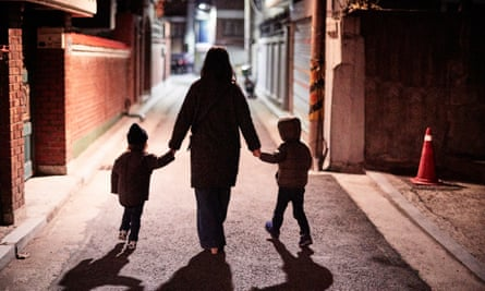Mother And Sons Walking On City Street