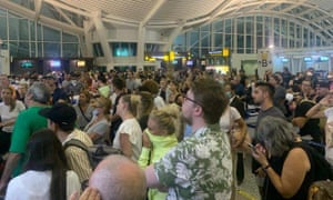 Travellers check for updates at Denpasar airport in Bali, as more than 100 British travellers have found themselves stranded due to the coronavirus travel restrictions.