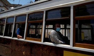 People wearing protective face masks are seen inside a tram at Alfama neighbourhood in Lisbon, Portugal.