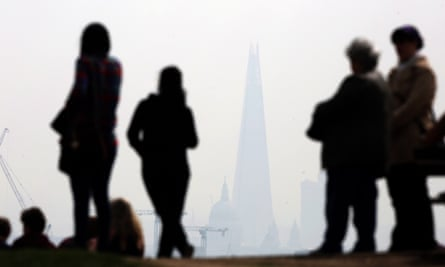 People stand on Parliament Hill in Hampstead Heath overlooking an overcast London skyline.