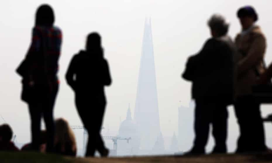 People stand on Parliament Hill in Hampstead Heath overlooking an overcast in Central London