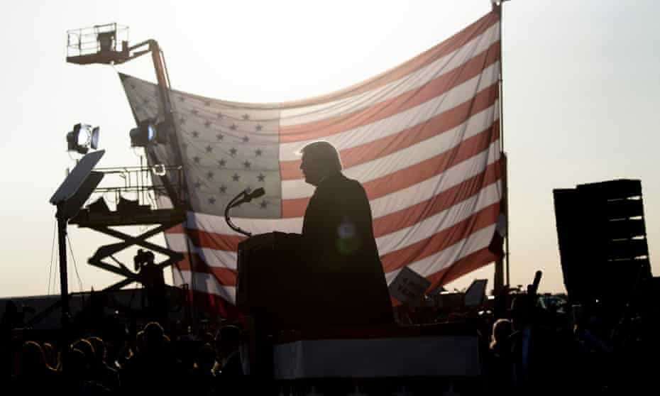 Donald Trump seen in silhouette against a US flag as he speaks during a rally in Minnesota in September.