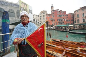 Gianni Colombo, aka Timbro, holds the flag of the winner at the end of the gondola regatta, held on the Grand Canal as part of Venice's Epiphany celebrations